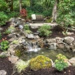 outdoor living area with pond and waterfall