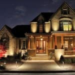 House and landscape illuminated by outdoor lights.