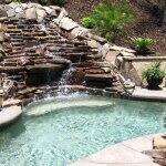 in-ground swimming pool with rock waterfall