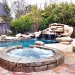 inground swimming pool with rock waterfall and spa
