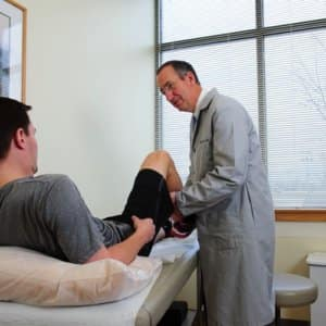 Chicago-based orthopedic surgeon Dr. Mark Bowen, seen here evaluating a patient who tore his ACL, does about 200 ACL reconstruction surgeries annually. (Photo courtesy of NorthShore University HealthSystem)