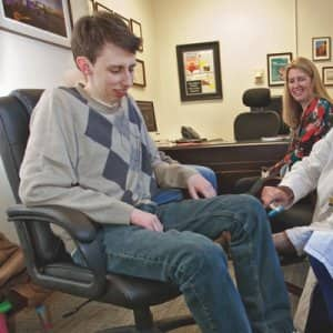 Dr. Jallo meets with Logan and his parents, Matt and Beth, to go over Logan's brain scans. (Photo by Robert Mang.)