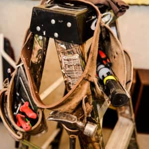 Home improvement contractor's tool belt on ladder during remodel