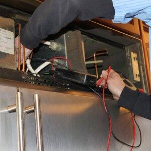 An All American Appliance employee checks a condenser fan motor while repairing a customer's refrigerator. (Photo courtesy of All American Appliance)