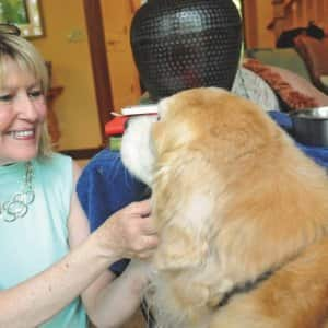 Wynn visits with Maggie, a 13-year-old golden retriever. (Photo by Roderick Vesper)