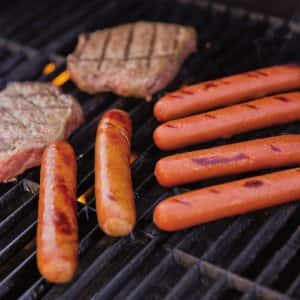 Grilling hotdogs and steaks outdoors.