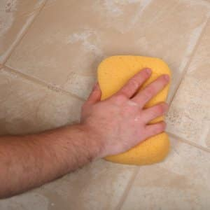 man's hand using sponge to clean tile