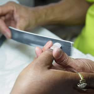 nail salon technician filing a customer's nails