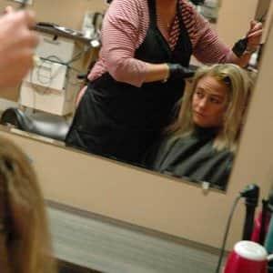 a hair stylist applies color dye to a woman's hair.