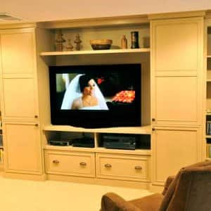 basement remodel with tv and bookshelves