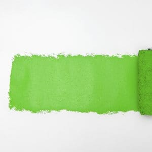 paint roller rolling green paint onto white wall
