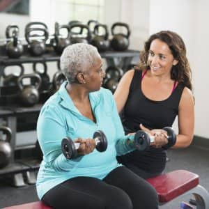 A personal trainer works out with a client in a gym. (Photo by Photo courtesy of iStock)