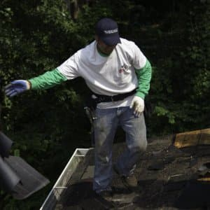 worker clearing off old roof materal