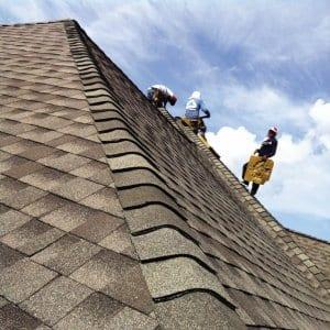 Workers Install Asphalt Shingles On Roof