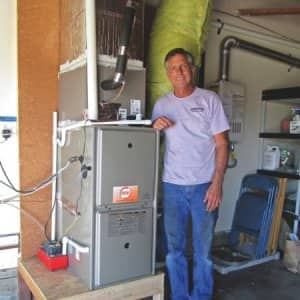 Owner Charlie Collins finishes work on a residential HVAC unit. (Photo courtesy of Central Heating & Air)
