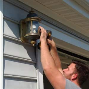 handyman using drill to screw light fixture onto garage