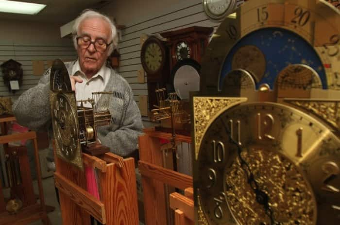 man inspecting old clock