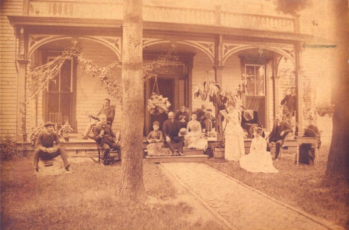 antique photo of a family in front of their home in the early 1900s