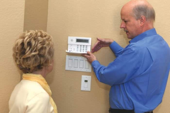 security company owner demonstrates alarm features to homeowner