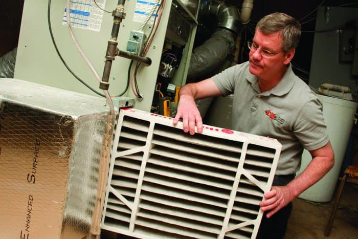 furnace technician installs filter