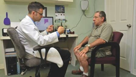 Audiologist Scott Sims consults with hearing aid patient Gerald Shaffer. (Photo by John Zambito)