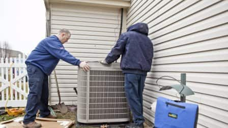 Two workers installing an a/c unit outside a home.