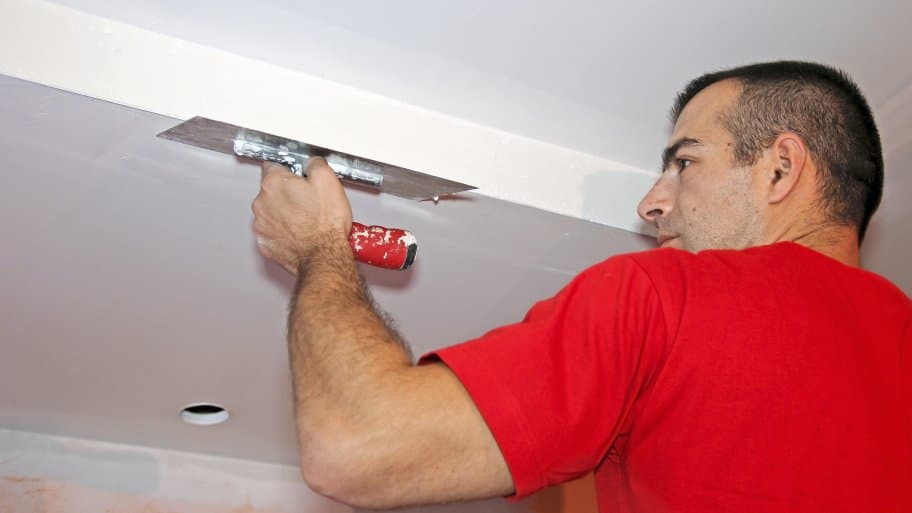 Contractor in red shirt skimming a ceiling