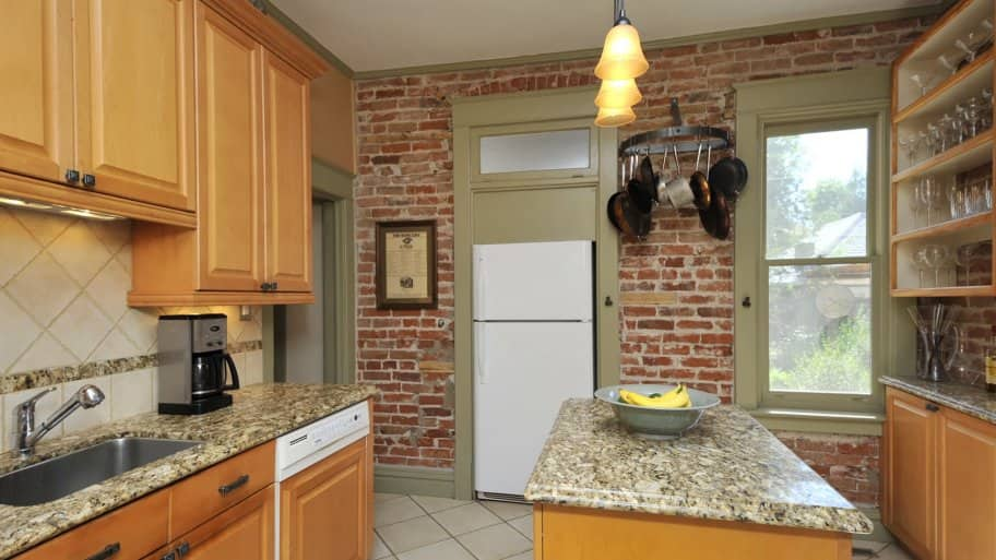 kitchen with wood cabinets, island and brick wall
