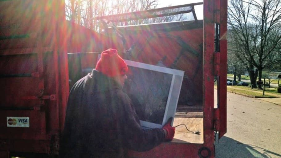 Julian Caldwell, of Junk King, loads a television into the truck for e-cycling. (photo courtesy of Junk King)
