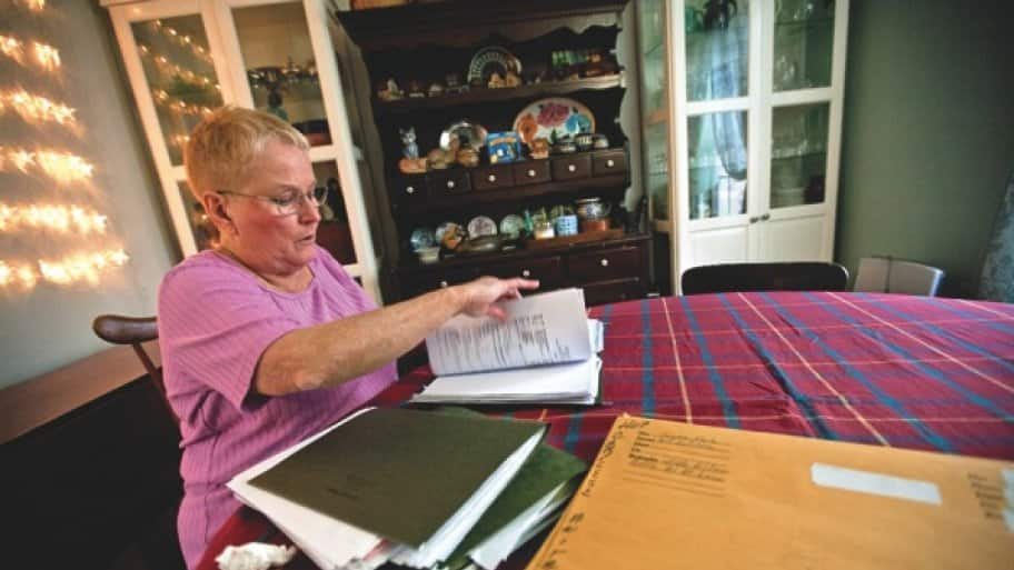 A woman looks through folders of medical records at a dining room table.