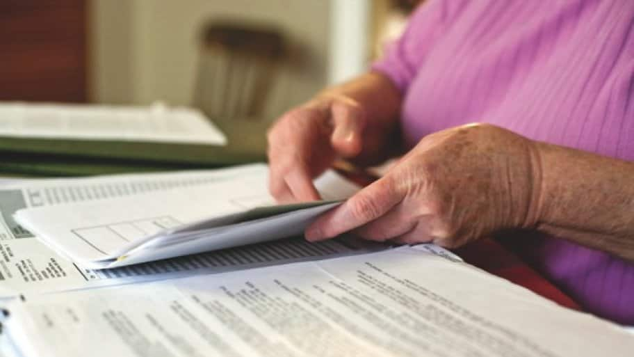 a woman leafs through papers at a table.
