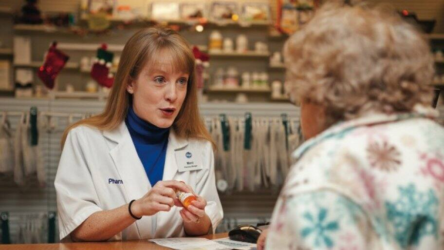 Kroger pharmacy manager Marci Kellar discusses prescriptions with Carolyn Litz, 84, of Indianapolis. (Photo by Brandon Smith)