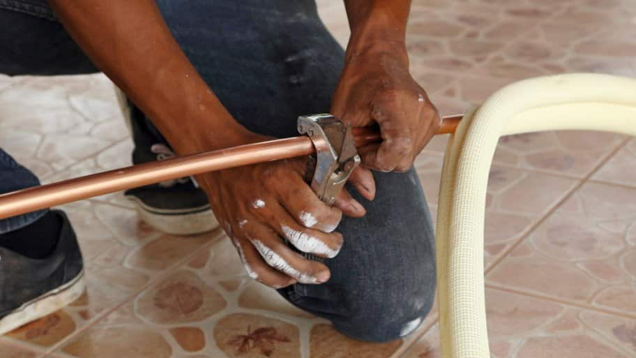 man cutting into copper pipe