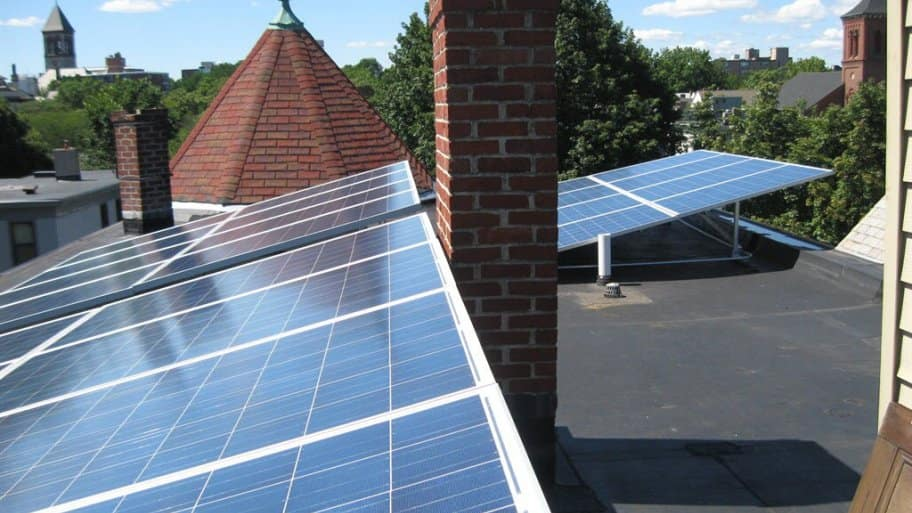 solar panels on a roof with brick chimney