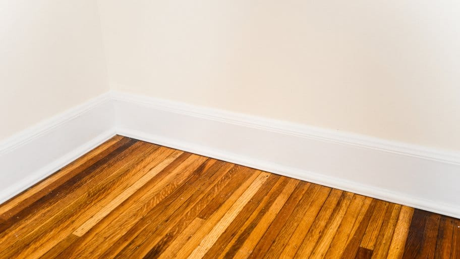 white baseboard on refinished hardwood floors