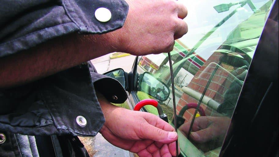man holding unlocking tool at vehicle window