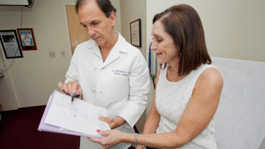 Plastic surgeon Dr. Leo McCafferty reviews a treatment plan with patient Sharon Nelson. (Photo by John Altdorfer)