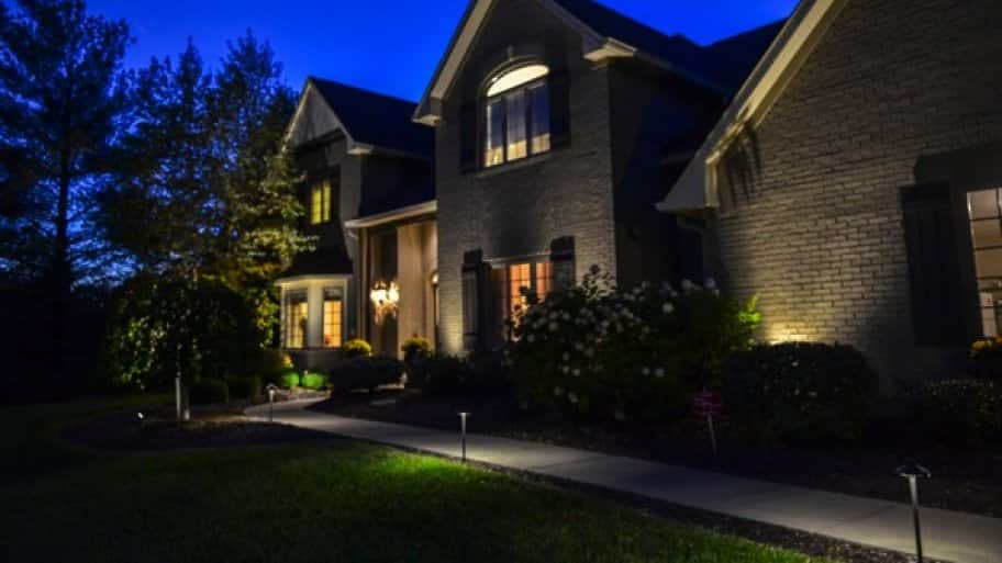 two-story brick home exterior lit up at night