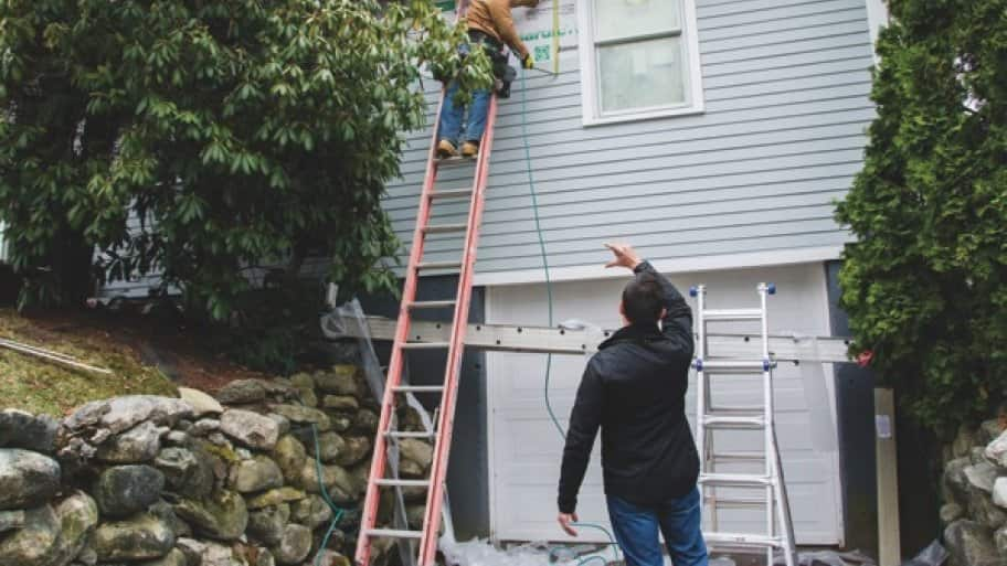 contractor supervises siding installation during home remodeling project