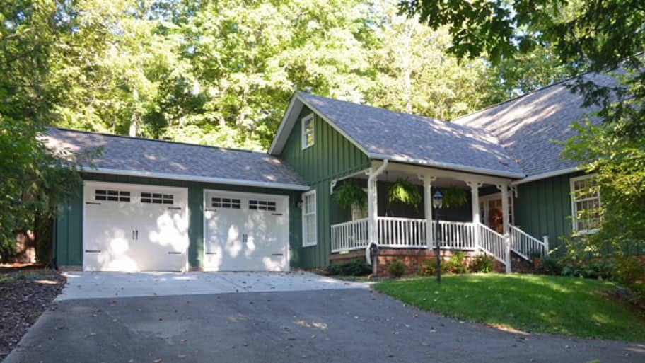 green house with carriage garage doors