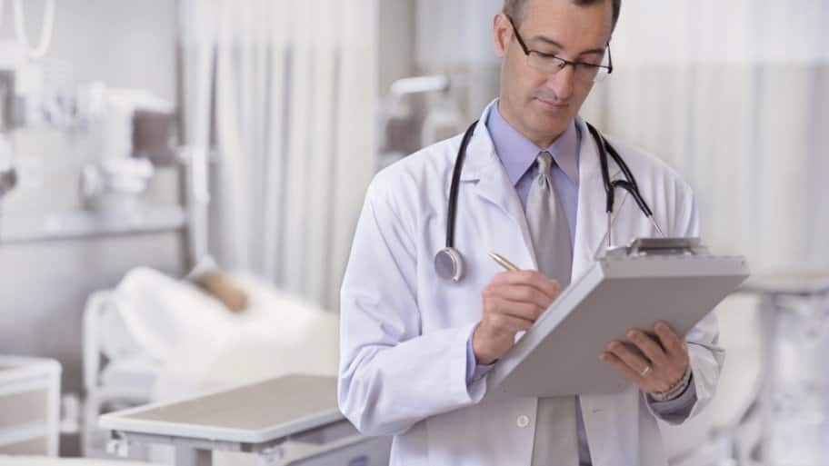 A doctor makes notes on a patient's chart while making rounds in a hospital room.