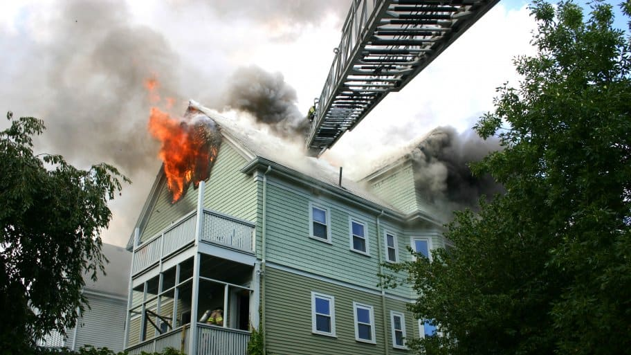 2-story house on fire with fire ladder extended to it
