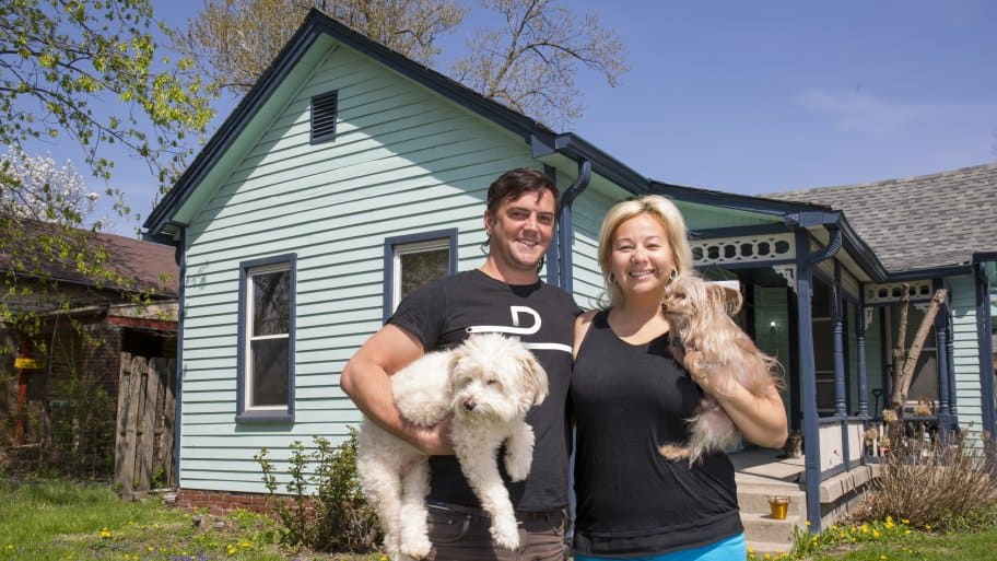 Angie's List Members Tad and Amity Aschliman holding their dogs, Champ and Nuni, in front of their Fountain Square home.