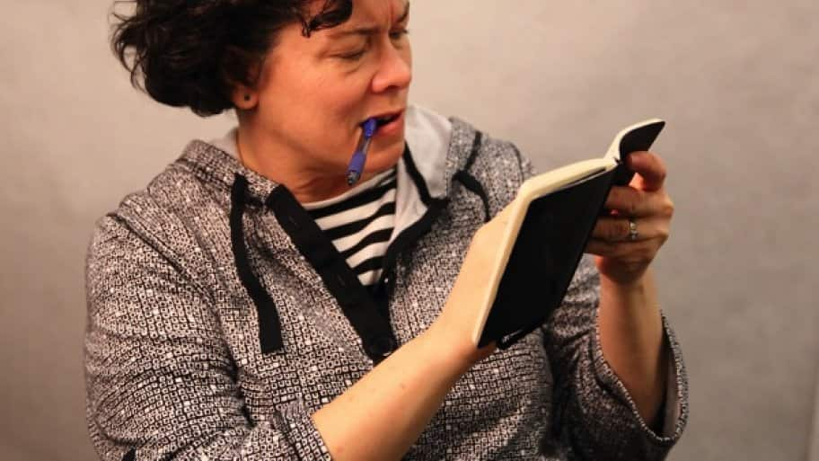 woman with pen in mouth squints at page in a book.