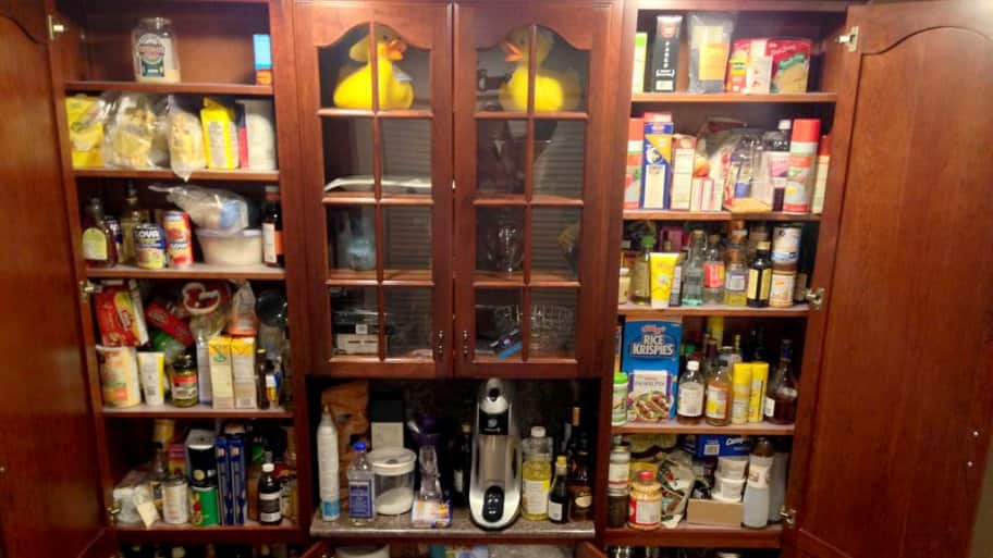Wooden kitchen cabinet pantry filled with grocery items. (Photo by Photo courtesy of Angie's List member Jeremy G. of New York)
