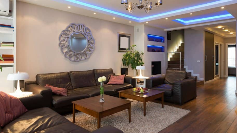 Living room with blue in-ceiling lighting and small recessed lights