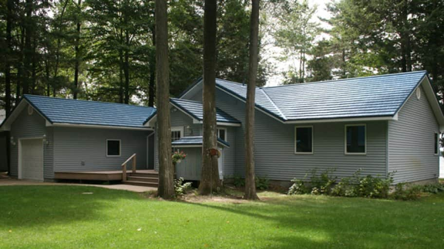 gray sided home with blue metal roof