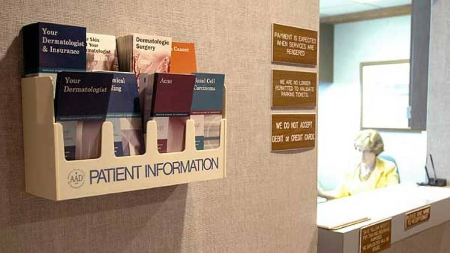 brochures on the wall in the receptionist area of a doctor's office.