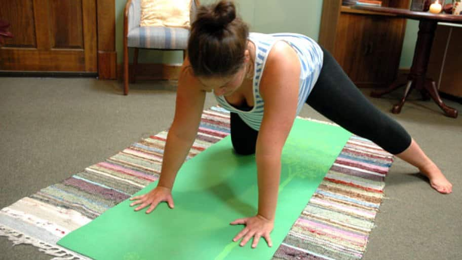 A woman with one knee on a yoga mat and the other leg extended.