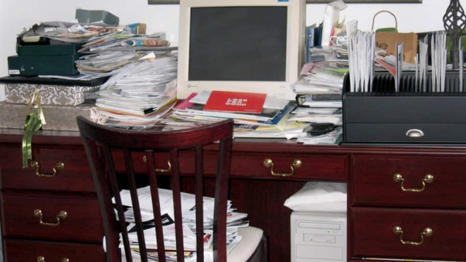 Desk with computer, piled high with stacks of papers.